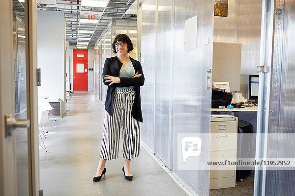 Porträt einer Geschäftsfrau im Bürokorridor stehend  die Arme verschränkt  lächelnd
