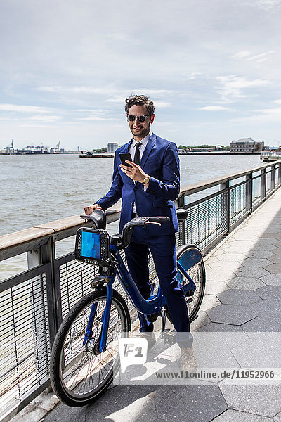 Young businessman on bicycle looking at smartphone along city river waterfront