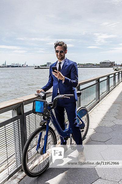 Junger Geschäftsmann auf dem Fahrrad schaut auf Smartphone am Ufer des Stadtflusses