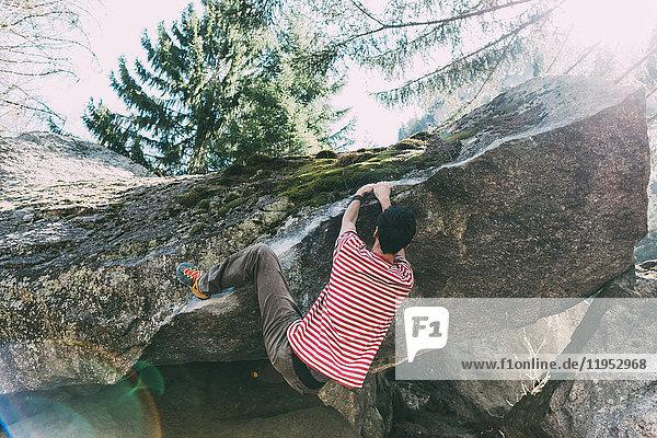 Männlicher Boulderer klettert Boulderüberhang  Lombardei  Italien
