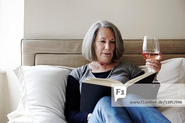 Ältere Frau mit grauem Bob sitzt auf dem Bett und liest Buch