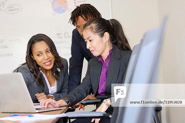 Geschäftsmann und Geschäftsfrauen im Büro  Blick auf Laptop-Bildschirm