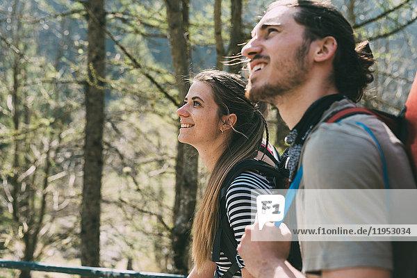 Zwei junge erwachsene Wanderer schauen im Wald nach oben  Lombardei  Italien