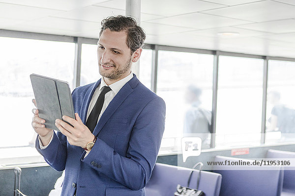 Junger Geschäftsmann betrachtet digitales Tablet auf Passagierfähre