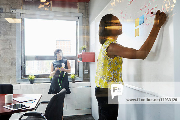 Two women in office  solving problem  using whiteboard  sticky notes stuck on whiteboard