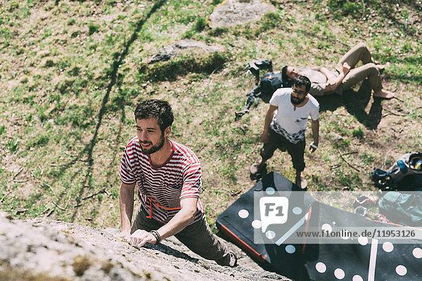 Hochwinkelaufnahme eines jungen männlichen Boulderers beim Klettern von Felsbrocken  Lombardei  Italien