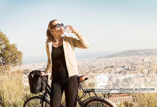 Woman drinking by bicycle  Barcelona  Catalonia  Spain
