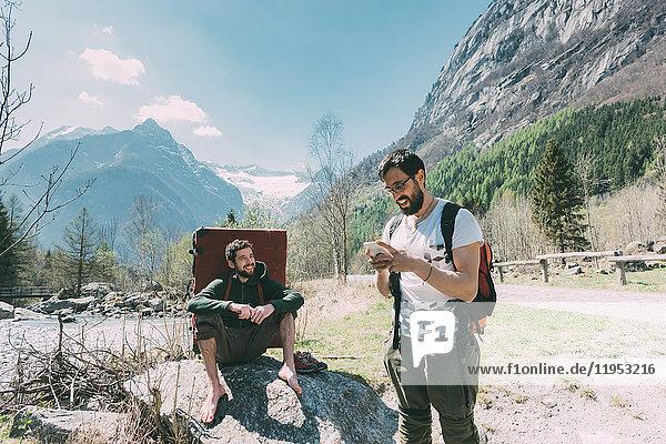 Zwei männliche Freunde mit Bouldermatten-Rucksack beim Blick auf Smartphone am Flussufer  Lombardei  Italien
