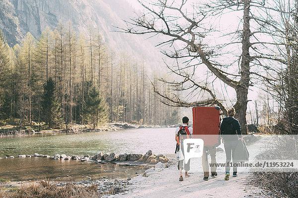 Rückansicht von erwachsenen Freunden mit Bouldermatten-Rucksack beim Wandern am Flussufer  Lombardei  Italien