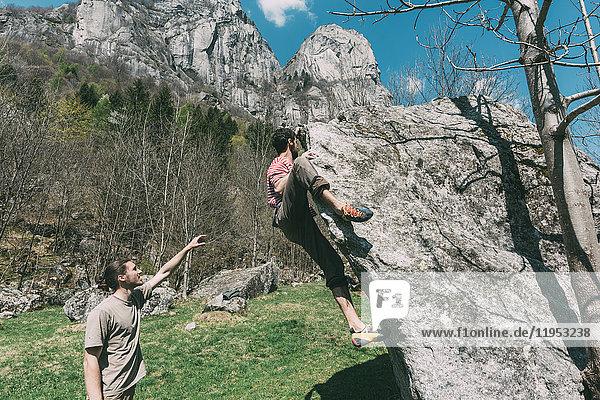 Junge männliche Boulderer zeigen auf Frauen beim Bouldern  Lombardei  Italien