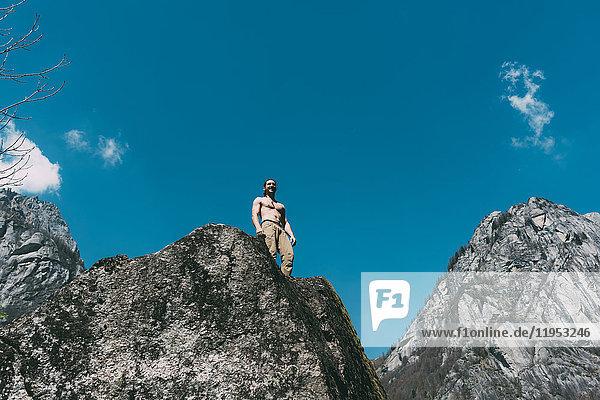 Tiefblick auf einen jungen männlichen Boulderer mit nackter Brust und Blick auf die Spitze eines Felsblocks  Lombardei  Italien