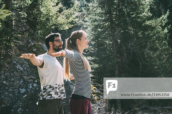 Mann und Frau praktizieren Yoga im Wald  Lombardei  Italien