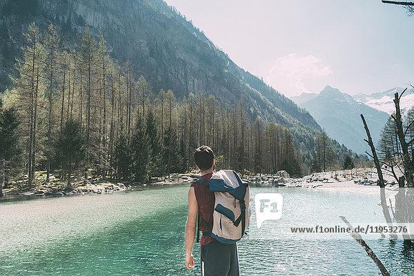 Rückansicht eines männlichen Wanderers mit Blick auf den Bergsee Lombardei  Italien