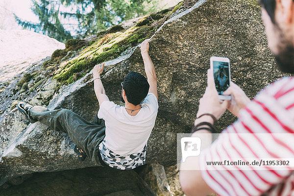 Männlicher Boulderer fotografiert Freund mit Smartphone  Lombardei  Italien