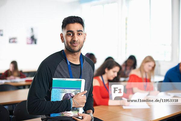 Porträt eines Schülers im Klassenzimmer  der ein Lehrbuch in der Hand hält und lächelnd in die Kamera schaut