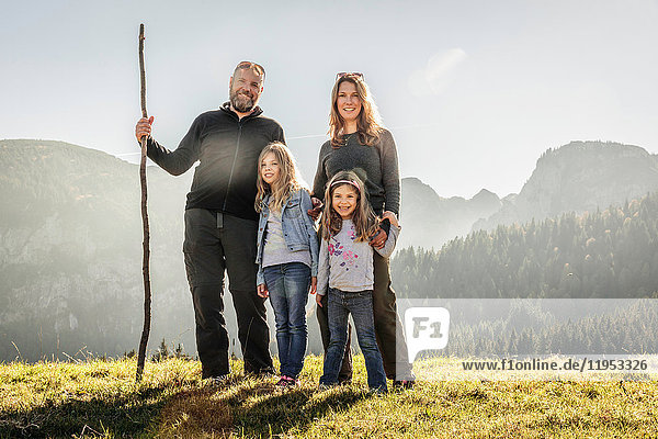 Porträt eines reifen Paares und zweier Töchter in sonnenbeschienener Berglandschaft  Bayern  Deutschland