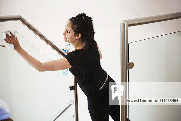 Woman standing on a staircase  cleaning a glass pane and banister rail.