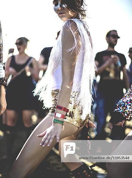 Junge Frau bei einem Sommer-Musikfestival  die in goldenen  mit Pailletten bestickten Hotpants unter der Menge tanzt.