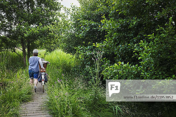 Rear view of woman pushing bicycle along path through tall grass.