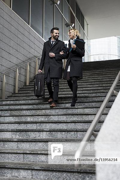 Glückliches Geschäftspaar in der Stadt beim Treppensteigen