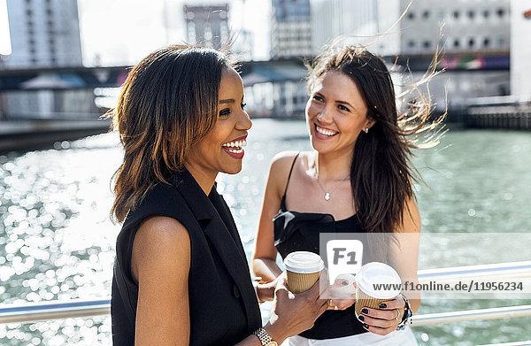 Two happy women having a coffee break on a bridge in the city