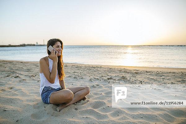 Junge Frau beim Telefonieren am Strand bei Sonnenuntergang