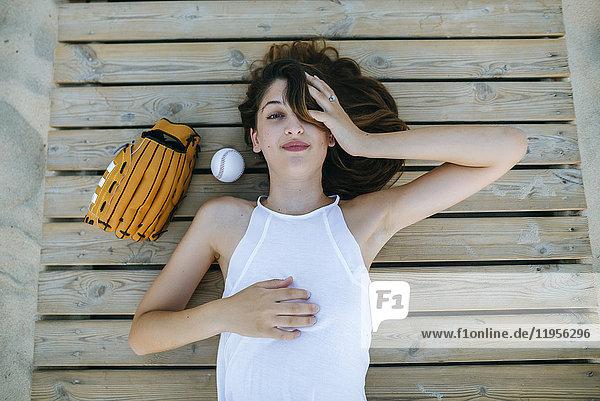 Junge Frau auf Holzweg neben Ball und Baseballhandschuh liegend