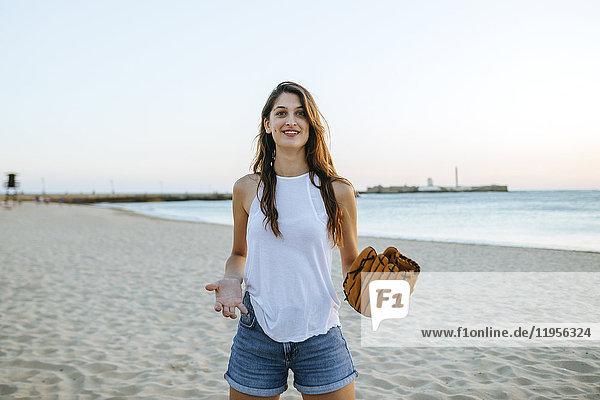 Junge Frau beim Spielen mit Baseballhandschuhen am Strand bei Sonnenuntergang