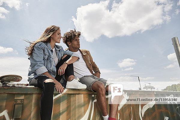 Junges Paar auf einer Wand sitzend