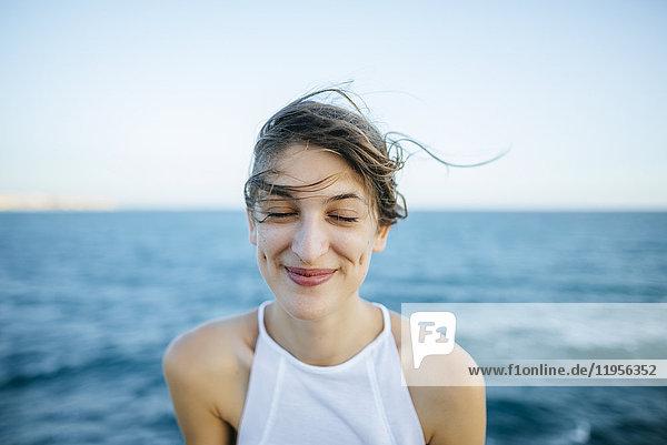Junge Frau lächelnd mit geschlossenen Augen und Meereshintergrund