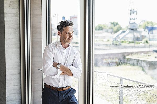 Porträt eines selbstbewussten Geschäftsmannes beim Blick durchs Fenster