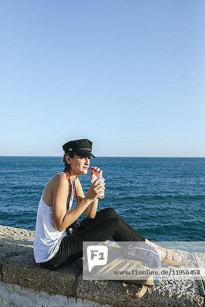 Junge Frau trinkt Smoothie am Meer