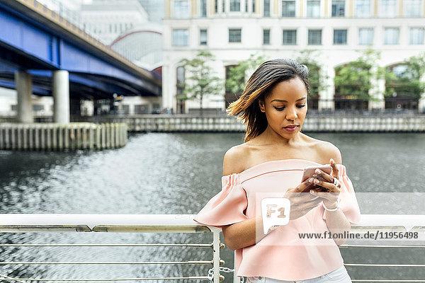 Frau sendet Nachrichten mit ihrem Smartphone in der Stadt