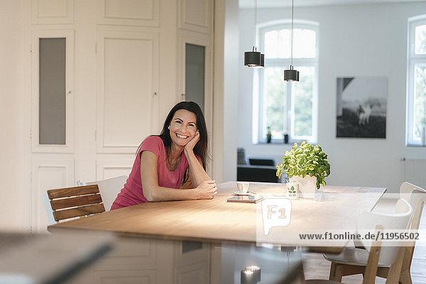 Porträt einer lächelnden Frau  die zu Hause am Tisch sitzt.