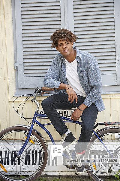 Junger Mann sitzt auf dem Fahrrad und schaut in die Kamera.