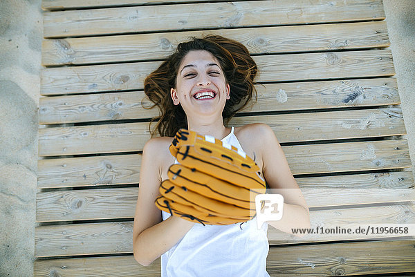 Junge Frau auf Holzweg liegend  lachend mit Baseballhandschuhen