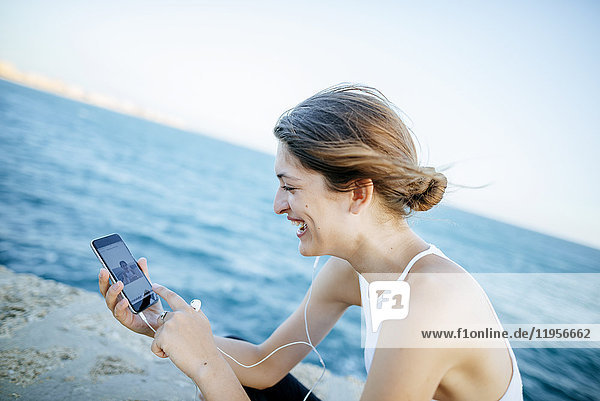 Junge Frau beim Betrachten von Fotos auf dem Smartphone am Meer