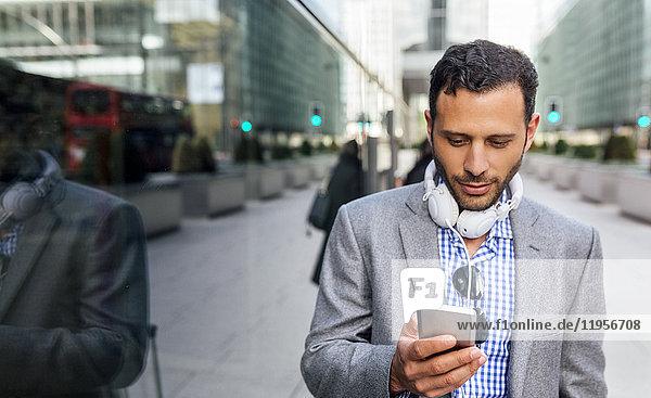 Geschäftsmann mit Kopfhörer und Handy in der Stadt