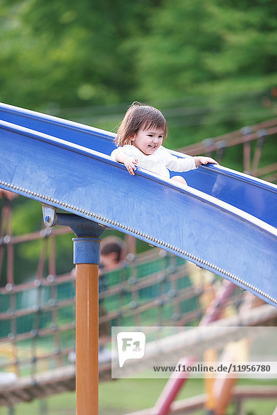 Mixed-race young girl playing on slide at the park