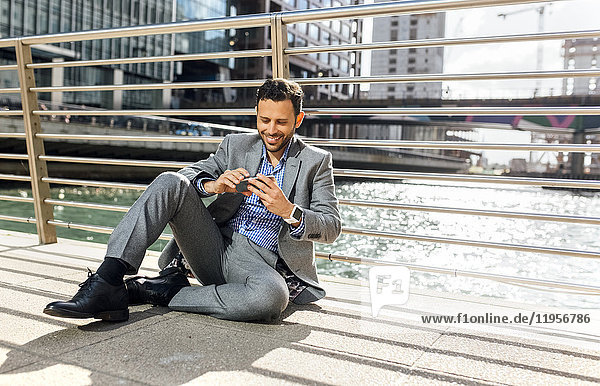 Businessman sitting on a bridge with cell phone in the city