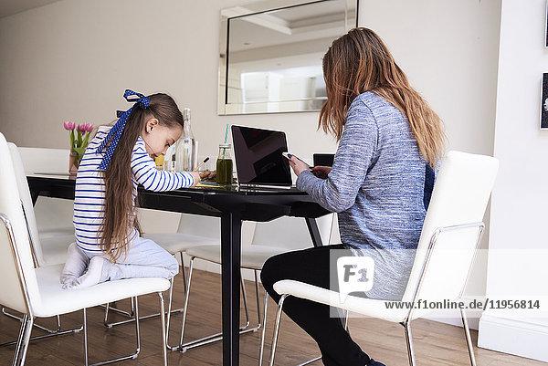 Kleines Mädchen beim Zeichnen am Tisch  während ihre Mutter mit dem Handy telefoniert.