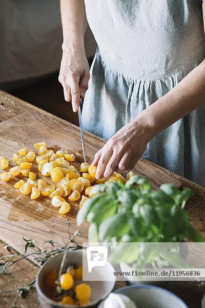 Nahaufnahme einer Frau beim Schneiden von frischen Tomaten