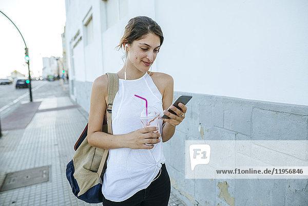 Junge Frau mit Handy und Smoothie geht die Straße entlang