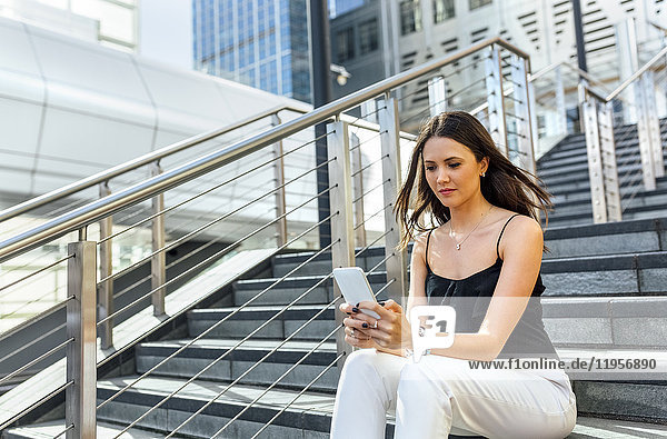 Junge Frau sendet Nachrichten mit ihrem Smartphone in der Stadt