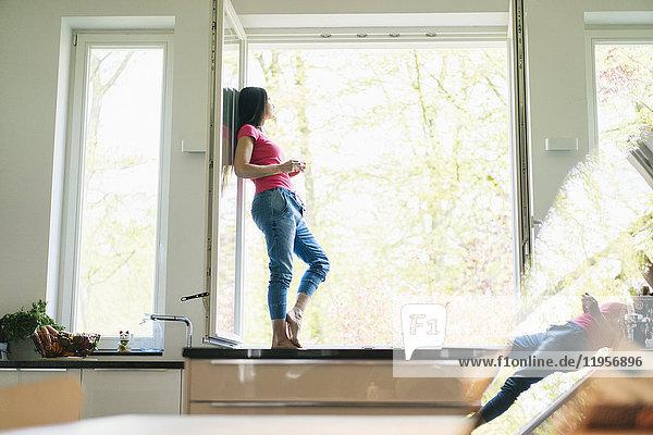 Frau steht in der Küche auf der Fensterbank