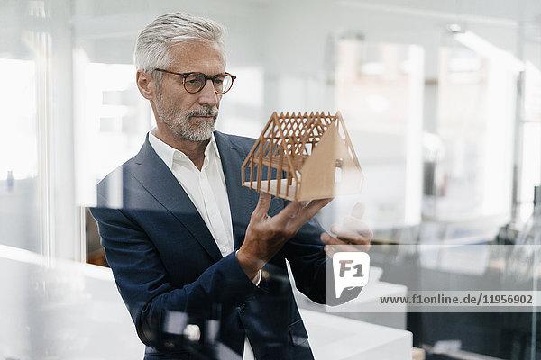 Ausgereifter Geschäftsmann untersucht Architekturmodell im Büro