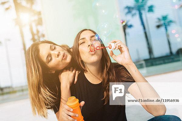 Zwei glückliche junge Frauen  die Seifenblasen blasen.