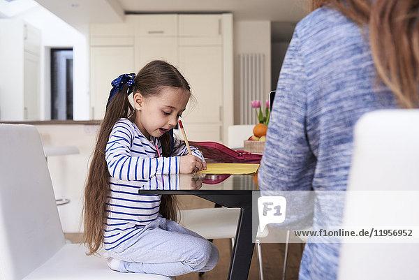Kleines Mädchen beim Zeichnen am Tisch zu Hause