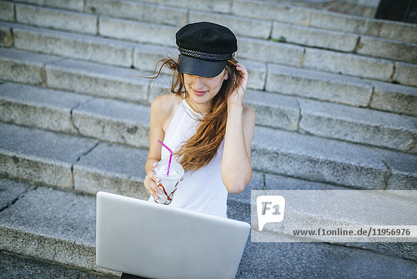Junge Frau mit Laptop und Smoothie auf der Treppe sitzend