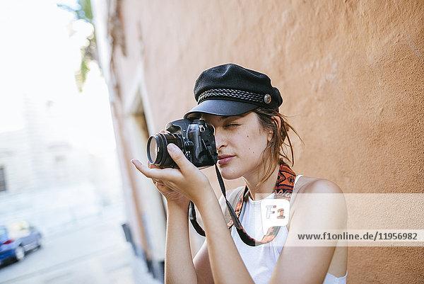 Junge Frau mit Hut fotografiert mit Kamera